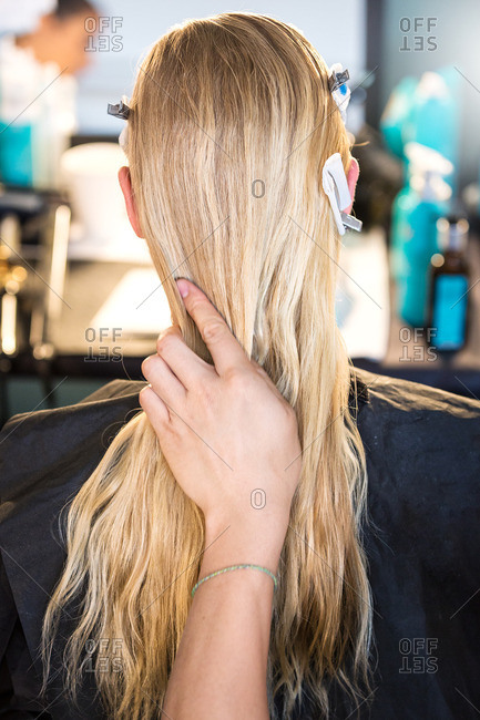 Hand styling blonde woman's hair