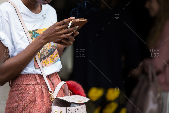 Woman smoking cigarette while using smartphone