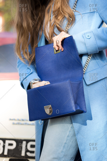 Woman wearing blue jacket with blue purse at the Vogue Festival in London