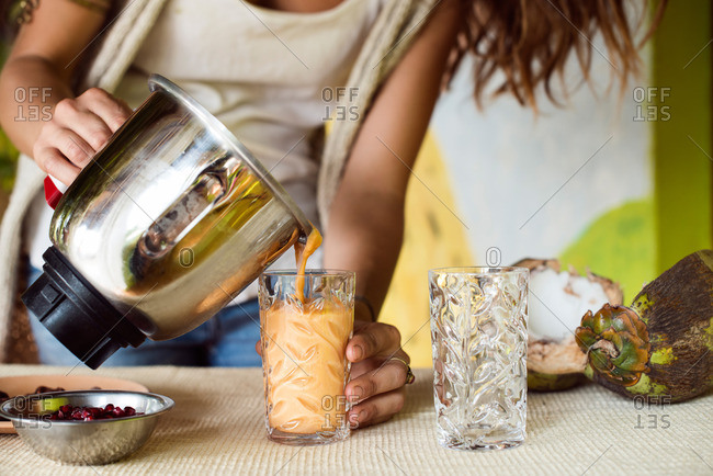 Woman pouring smoothie into a glass