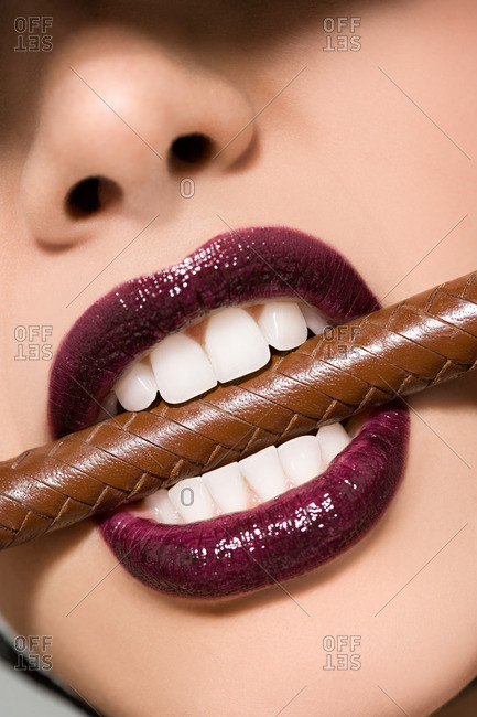 Woman biting brown leather stick