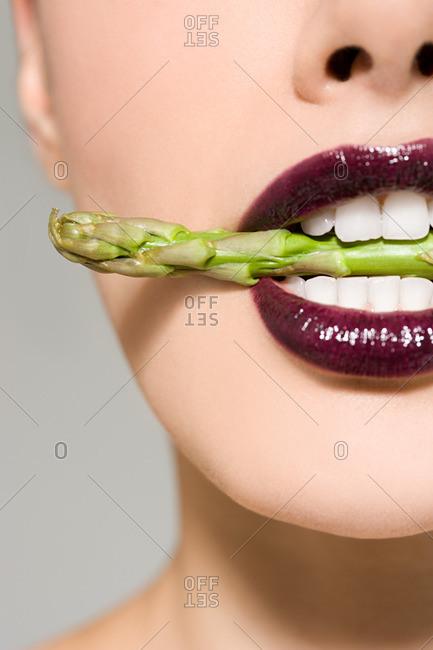 Woman biting asparagus