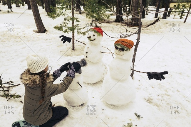 Girl putting a hat on a snowman