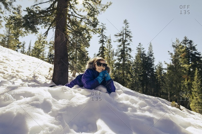 Girl lying down on a snow covered hill smiling