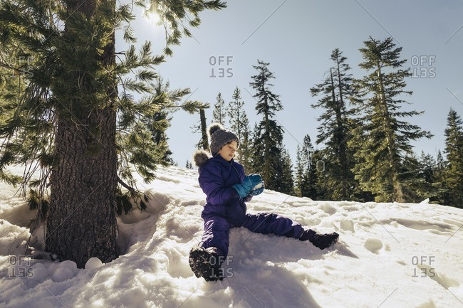Girl sitting down on a snow covered hill making a snowball