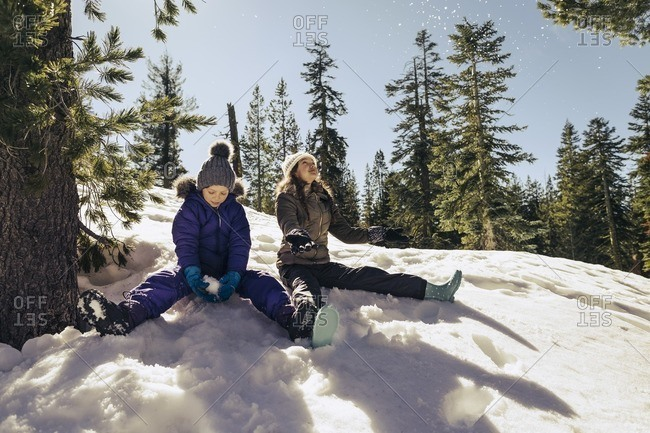 Girls sitting down on a snow covered hill making snowballs