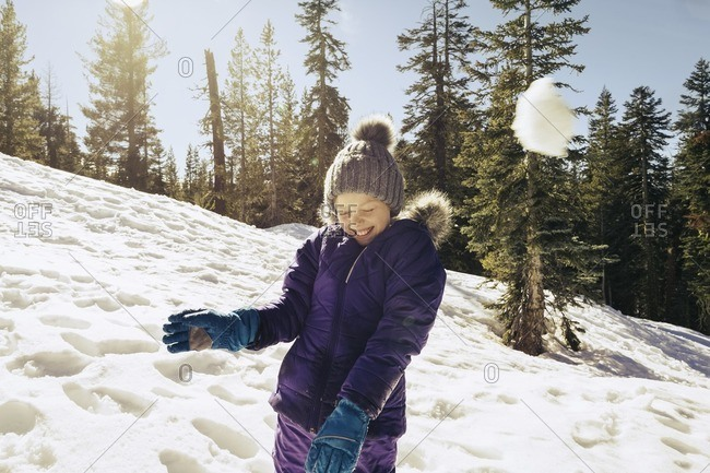 Girl having a snowball fight on a wooded hillside