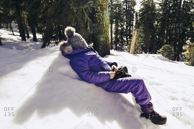 Girl lying down on a snow covered hill resting
