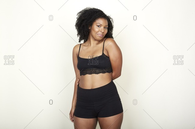 Woman with curly hair in black sports bra and shorts