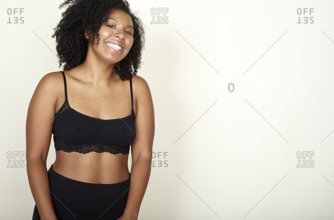 Portrait of a woman in black bra and shorts with a big smile