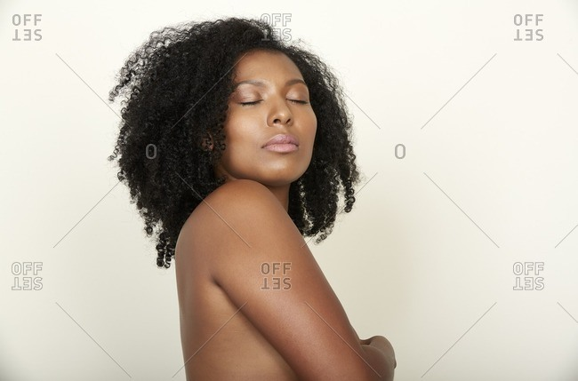 Nude woman standing with arm across her chest and eyes closed