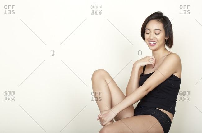 Woman wearing black tank top and panties laughing