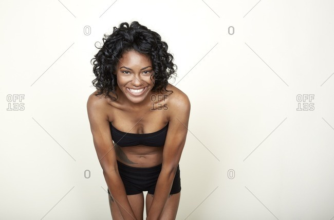 Woman wearing black bra and shorts leaning forward
