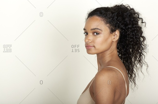 Side view of a woman with a curly ponytail and a beauty mark