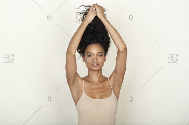 Woman with a beauty mole lifting up her curly hair