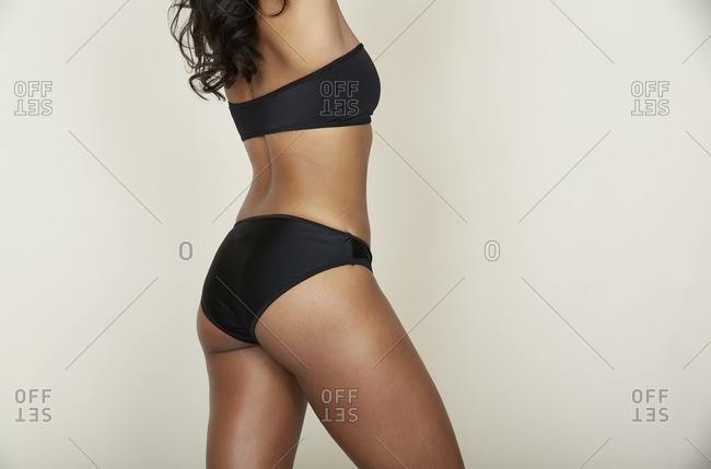Rear view of woman's body wearing black strapless bra and panties