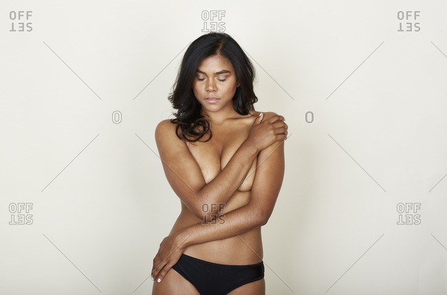 Woman standing with arm across her bare breasts