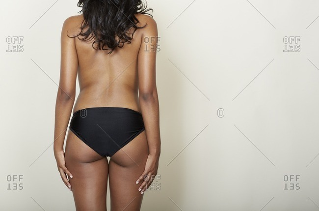 Rear view of topless woman wearing black panties