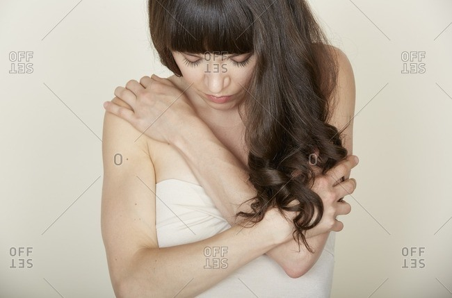 Woman with long brown hair wrapping her arms around herself