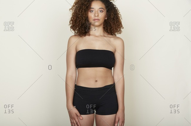 Woman with a nose ring and curly hair in a black bra and shorts