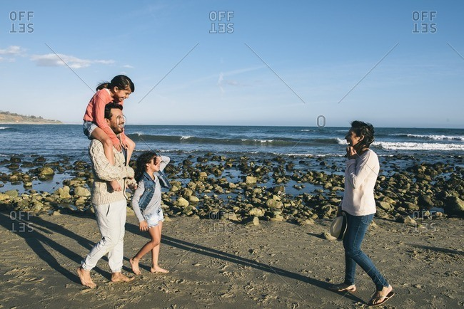 Parents with two girls on rocky beach in California