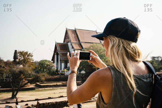 Woman taking photo with smartphone at historic site