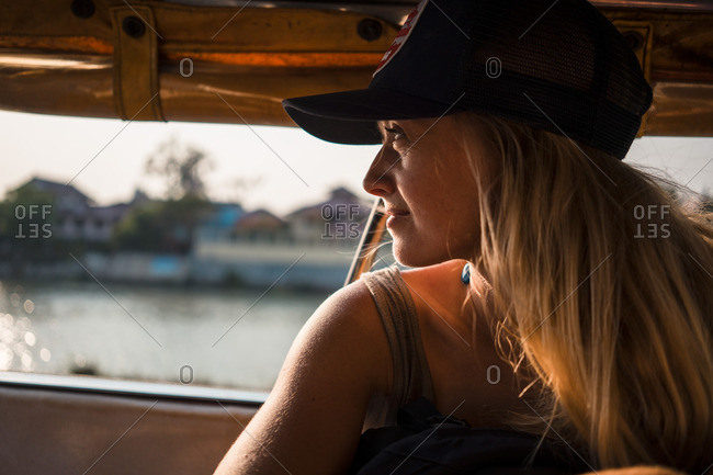 Woman riding in a water taxi at dusk