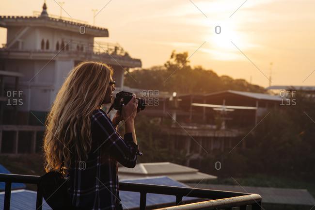 Tourist taking photos at dusk in Southeast Asia