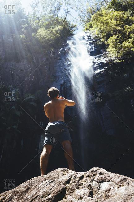 Man taking photo of waterfall from rock below
