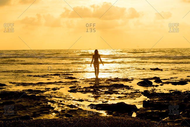 Silhouette of a woman walking alone along a beach at sunset