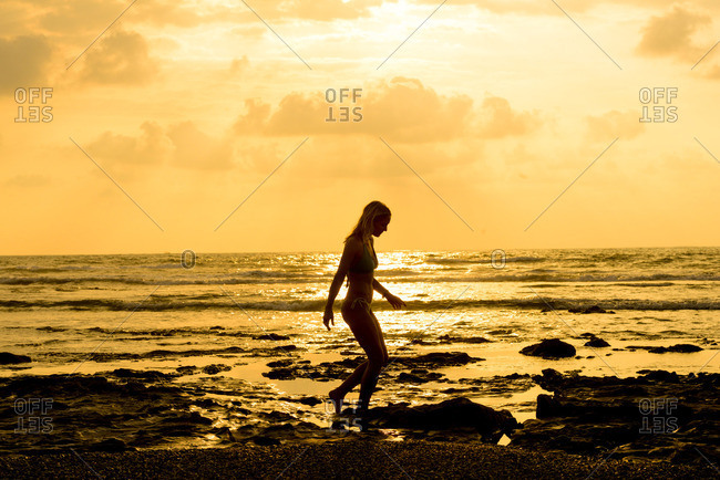 Silhouette of a woman walking along a beach at sunset