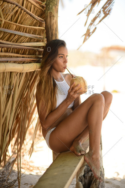 Woman sitting in a beach cabana drinking a beverage from a coconut