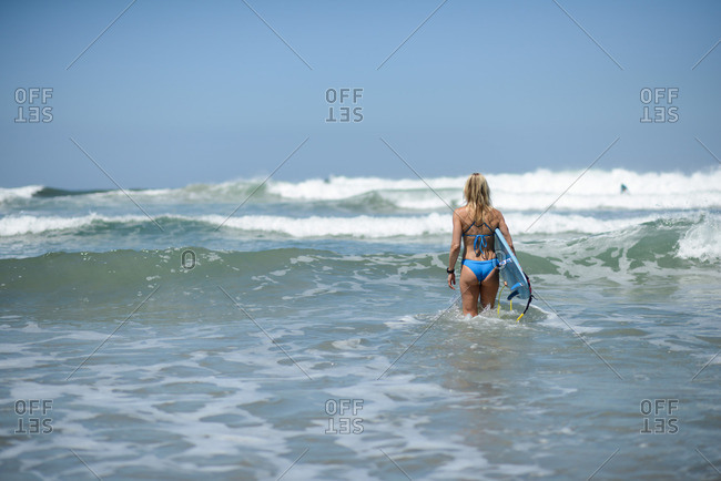 Woman standing in the surf with a surfboard waiting to catch a wave