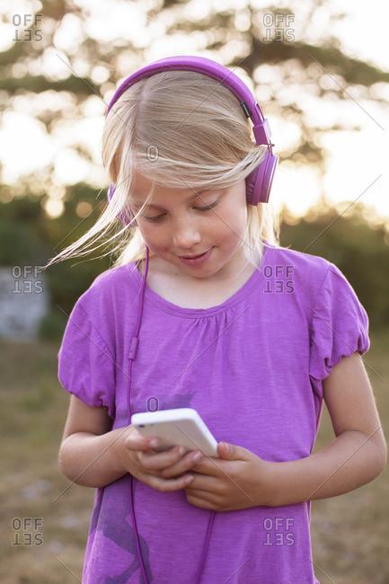 Sweden, Gotland, Faro, Girl listening to music from smart phone