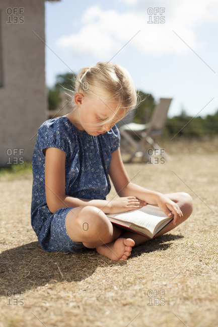Sweden, Gotland, Faro, Girl reading book sitting in backyard