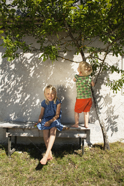 Sweden, Gotland, Faro, Girl with brother on back yard bench