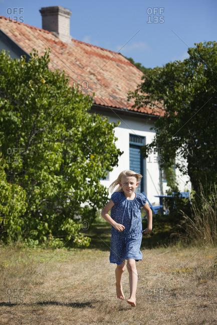 Sweden, Gotland, Faro, Girl running across back yard