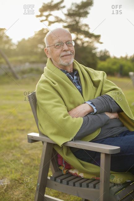 Sweden, Gotland, Faro, Portrait of senior man sitting in chair outdoors