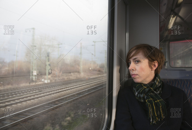 Germany, Mid adult woman on train looking through window