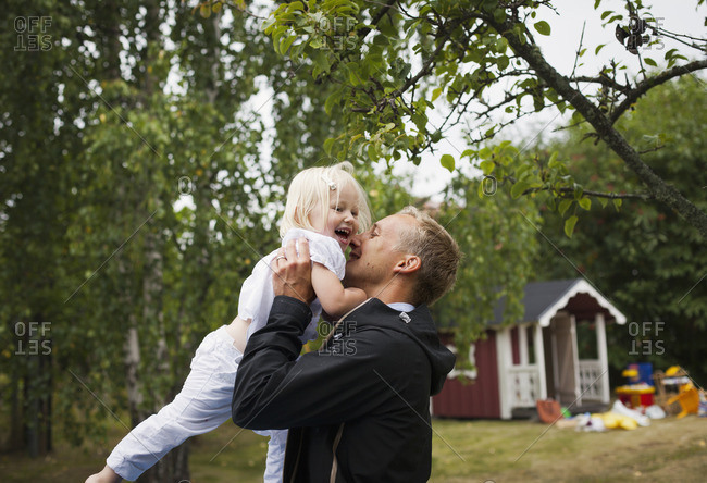 Sweden, Uppland, Father holding up daughter