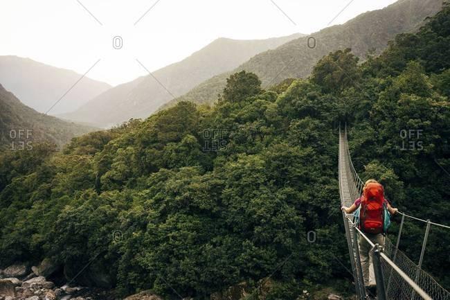 New Zealand, South Island, Hiker crossing footbridge