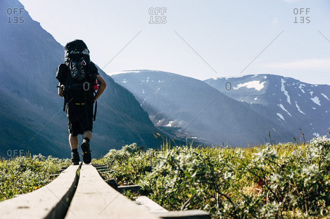 Sweden, Lapland, Ladtjovagge, Kungsleden, Rear view of male hiker walking along boardwalk
