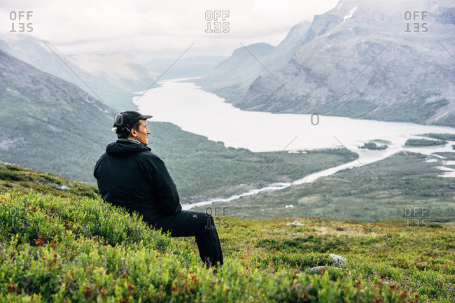 Sweden, Lapland, Kaitumjaure, Kungsleden, Male hiker sitting and looking at river in mountain valley