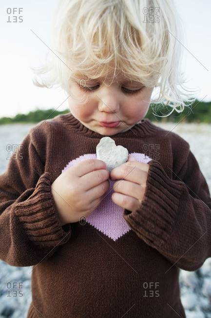 Sweden, Gotland, Gnisvard, Girl with heart shape stone