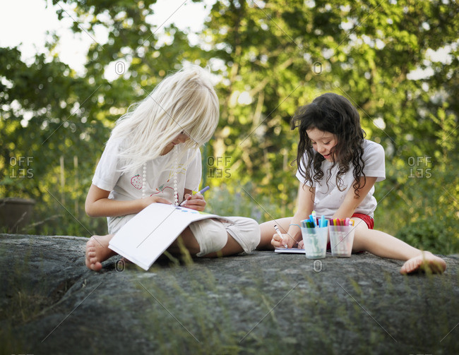 Sweden, Two girls sitting on rock, drawing