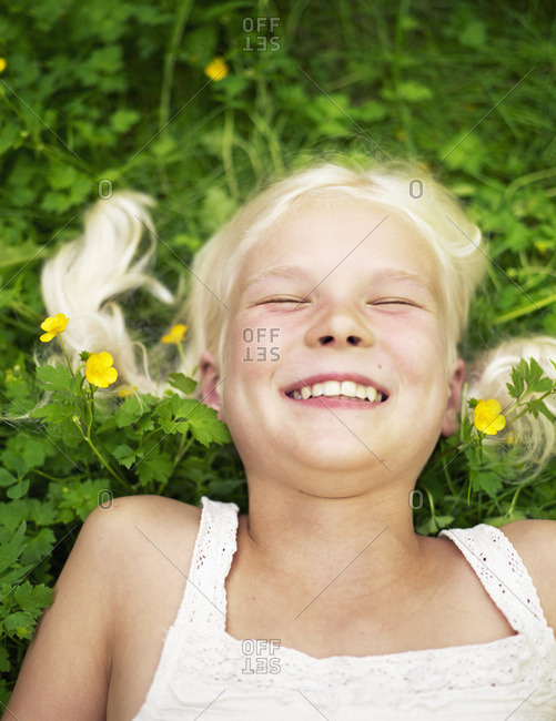 Sweden, Sodermanland, Young girl lying on grass