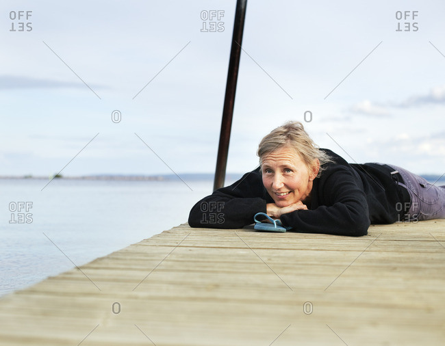 Sweden, Ostergotland, Mature woman lying down on wooden jetty