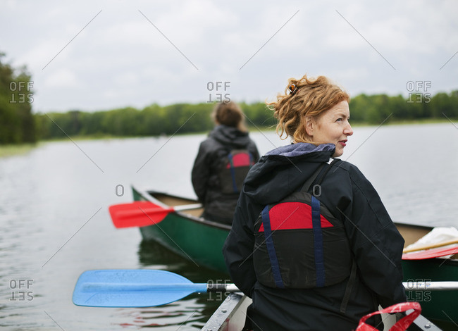 Sweden, Stockholm Archipelago, Uppland, Varmdo, Two women canoeing across lake
