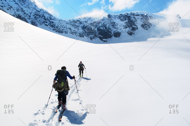 Norway, Kungskrona, Sundalsora, Pair of people telemark skiing in mountain scenery