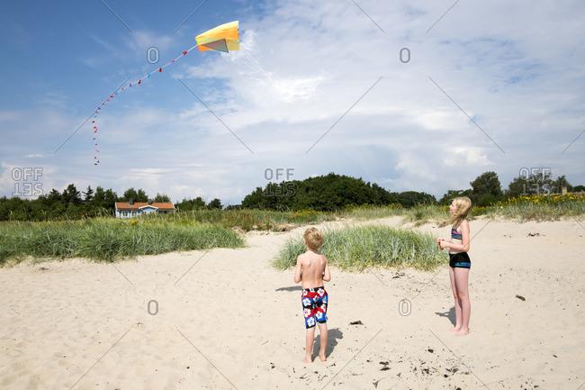 Sweden, Skane, Vejbystrand, Boy and girl flying kite